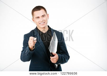 Smiling businessman holding clipboard and pointing at camera isolated on a white background