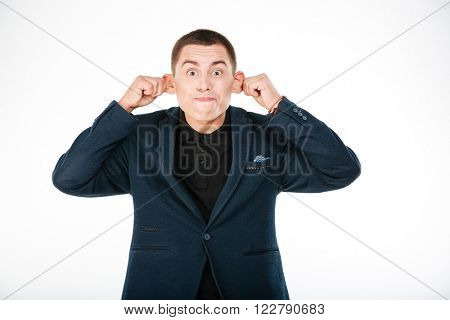 Funny businessman holding his ears isolated on a white background