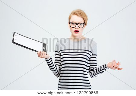 Woman holding clipboard and shrugging shoulders isolated on a white background