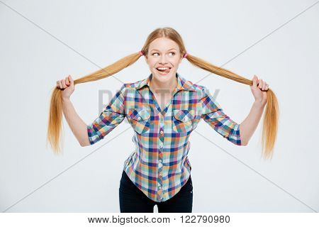 Funny young woman holding her ponytail and showing tongue isolated on a white background