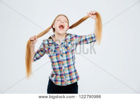Young woman holding her ponytails and screaming isolated on a white background