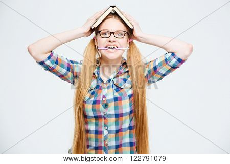 Funny female student with book on head biting pen isolated on a white background