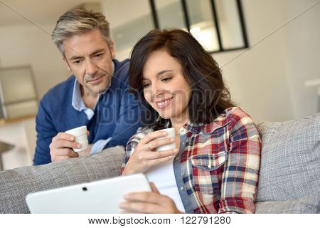 Couple at home websurfing with digital tablet