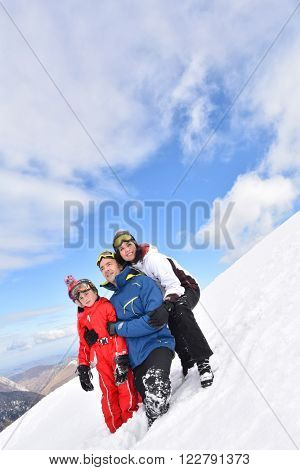Portrait of family having fun walking down snow slope