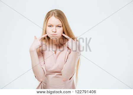 Woman with inflated cheeks posing isolated on a white background