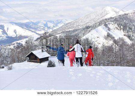 Family running down slope in snowy mountains