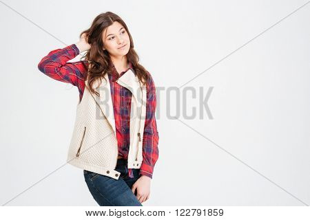 Pensive pretty young woman in plaid shirt and waistcoat standing and touching her hair over white background