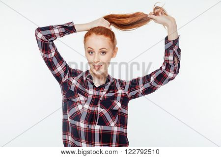 Redhead woman holding her ponytail and showing her tongue isolated on a white background