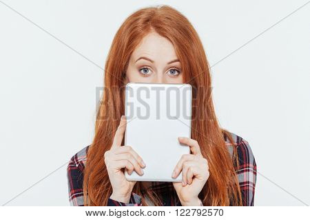 Redhead woman peeking from tablet computer isolated on a white background