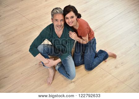 Upper view of couple sitting on wooden floor