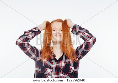 Relaxed redhead woman with closed eyes holding her ponytails isolated on a white background