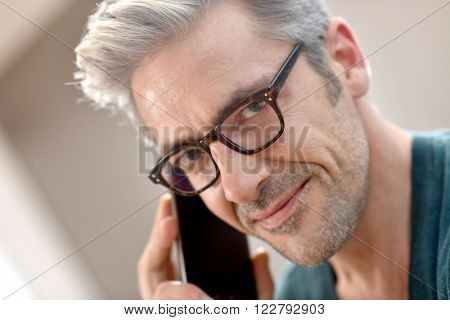 Mature handsome man with eyeglasses talking on phone