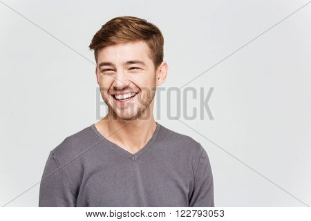 Portrait of cheerful attrative young man in grey pullover over white background