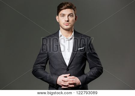 Portrait of serious confident young businessman in black suit and white shirt over grey background