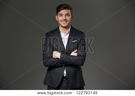 Cheerful successful young businessman in black suit standing with arms crossed  over grey background