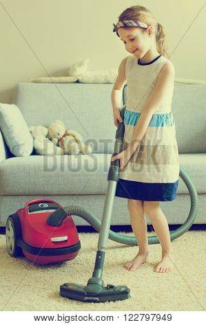 Cute little girl cleaning carpet with vacuum cleaner. Vintage effect.