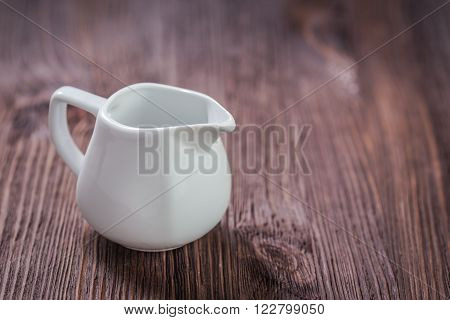 White ceramic teapot creamer and sugar bowl on dark wooden background