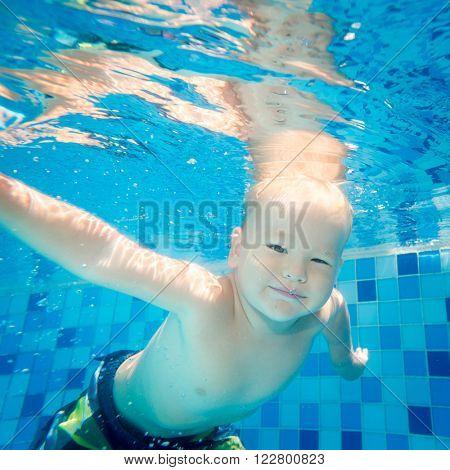 Cute caucasian boy enjoys swimming underwater