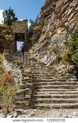 Trekker ascending stone steps. Annapurna circuit in Nepal.