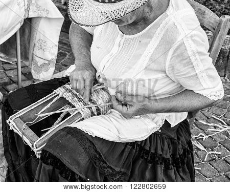Trento, Italy - January 2, 2016: Elderly lady builds bags woven by hand using the dried leaves of the corn cobs.