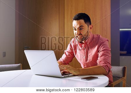 Male angry student work on computer touch pad young angry business man use laptop sitting at wooden table of home angry freelancer working on notebook at kitchen. angry entrepreneur and furious