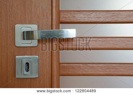Silver modern door handle on brown wooden door with milky white translucent glass