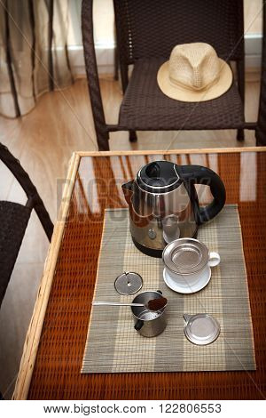 Morning coffee served in vietnam coffee filter on rattan table with two rattan chairs natural light photo