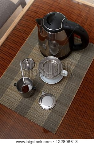 Morning coffee served in vietnam coffee filter on rattan table with two rattan chairs natural light photo closeup