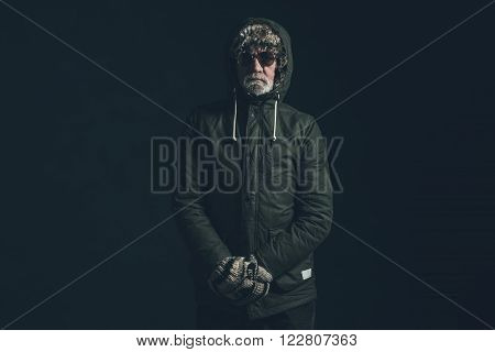 Senior Man With Gray Beard Wearing Dark Green Winter Coat With Hoody.