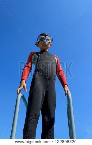Young boy ready for diving in diving suit puts on diving mask portrait against blue sky on sunny day