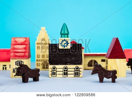 Figurine wooden hometown buildings on blue background
