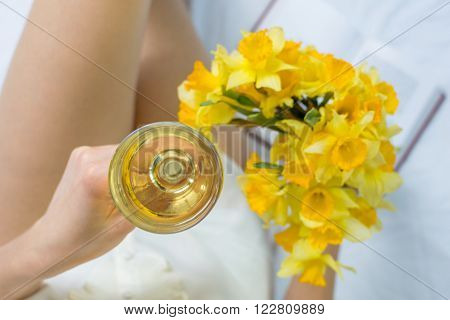 Woman with narcissus and wine in bed
