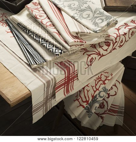 Folded Napkins And Tablecloth Of Various Designs On Table And Stool