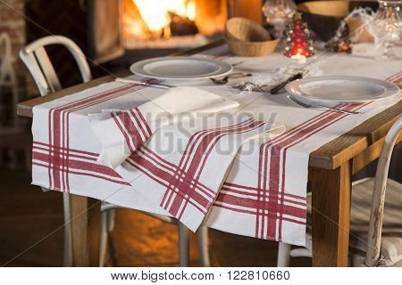 Set Dinnerware And Tablecloth With Red Stripes Near Blazing Fireplace