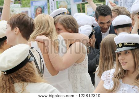 STOCKHOLM SWEDEN - JUN 10 2015: Group of happy teenages wearing graduation caps hugging and celebrating the graduation after finishing high school at the school Globala gymnasiet June 10 2015 Stockholm Sweden