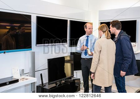 Salesman showing flat screen television to young couple in electronics store