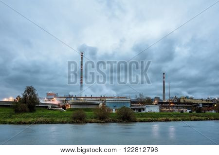 Pulp mill on the banks of the river. Image pulp mill for the production of paper, smoke from the chimneys. Paper production harms the environment, emission of harmful substances into the air.