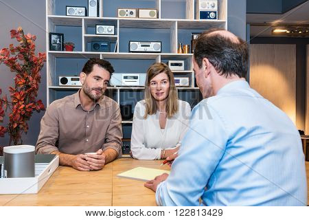 Young couple looking at salesman making sale receipt in electronics store