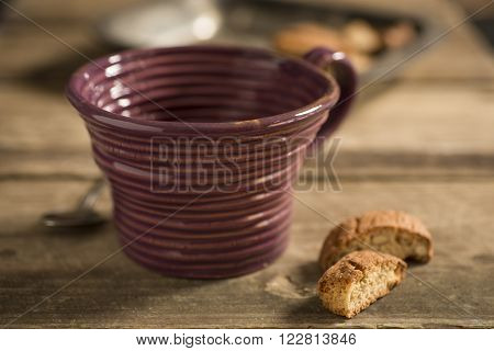 Empty Brown Teacup Between Spoon And Biscuits