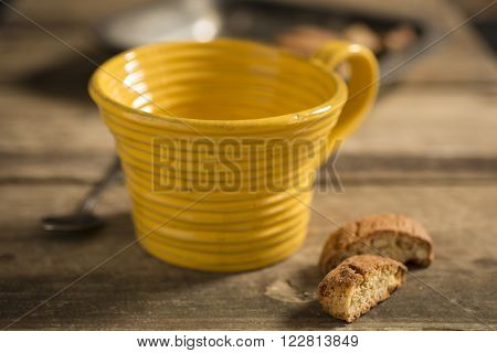 Empty Yellow Teacup Between Spoon And Biscuits