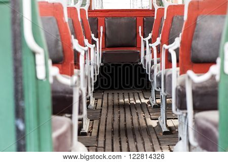 View down the aisle of the colorful red framed interior seating on a vintage bus