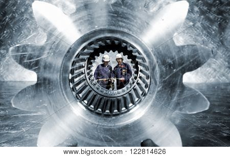 two industry workers seen through a giant cogwheels axle, slight blue toning
