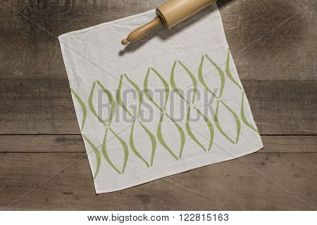 Square Table Napkin With Green Concave Lines Alongside Rolling Pin