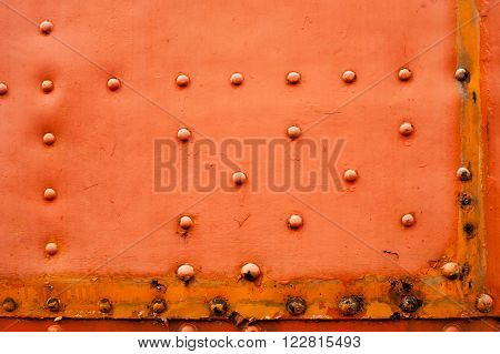 Old faded red metal background with a random pattern of studs corrosion and rust in a full frame view