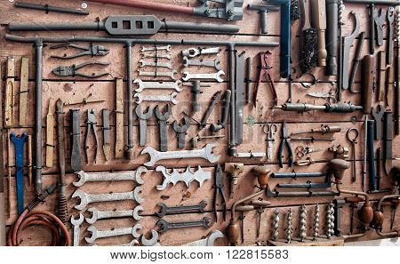 Display of various iron wrenches drill bits clamps and other tools on old wooden wall
