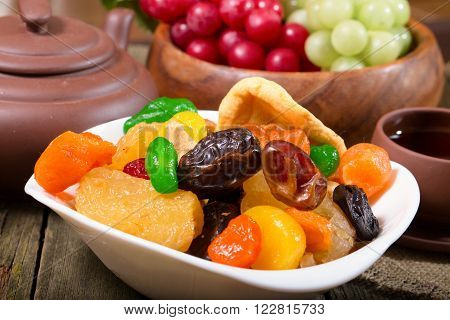 Plate with dried fruit and tea-things. Rural style close up small depth of sharpness