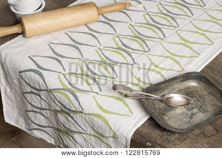 White Towel With Concave Line Design Alongside Rolling Pin