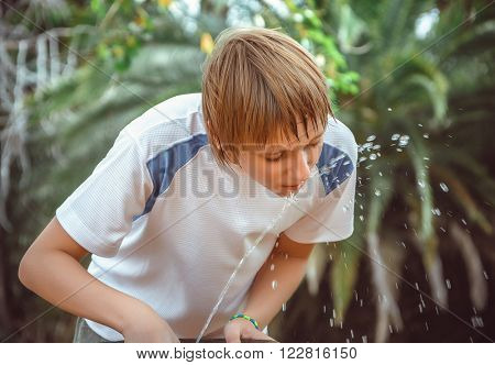 boy drinking water from a fountain