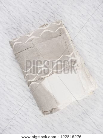 Folded Gray Duvet With White Concave Line Design On Marble