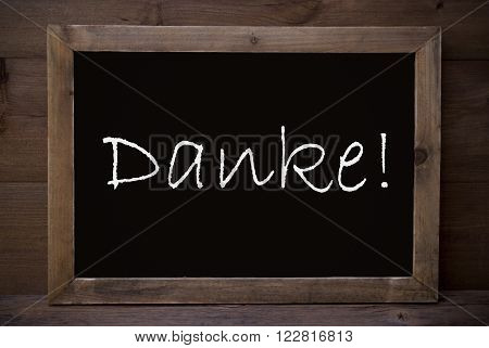 Brown Blackboard With German Text Danke Means Thank You As Greeting Card. Wooden Background. Vintage Rustic Style.